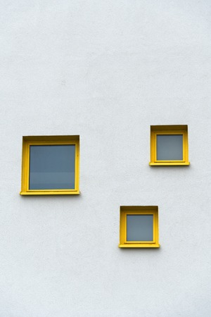 exterior modern design three yellow frame window on white concrete cement wall of building achitecture background