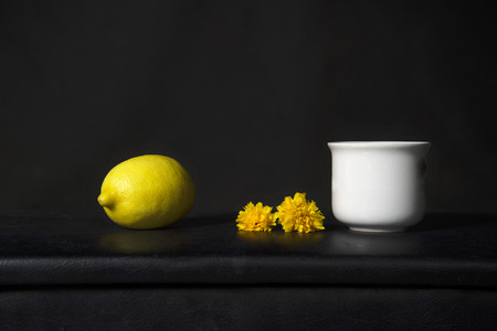 yellow lemon with orange flower and white ceramic cup in classic baroque still life fruit food design dark black background