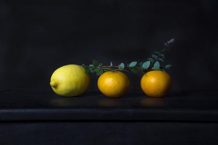 yellow lemon with orangeand green leave in classic baroque still life fruit food design dark black background