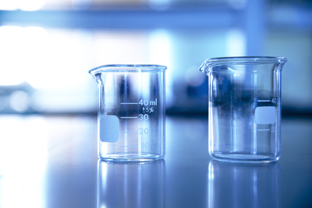 two glass beaker in chemical education technology science laboratory blue background