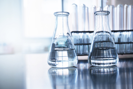 two clear flask with water in front of test tube in education chemistry science blue laboratory background 版權商用圖片