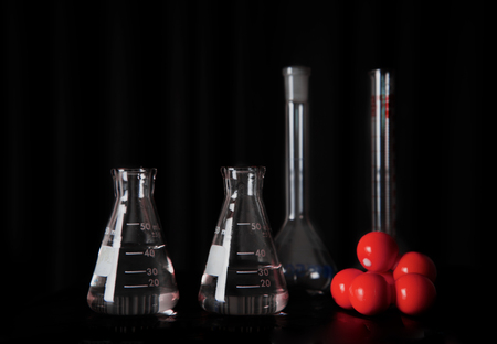 medical research science glass flasks with water and red chemical molecular structure still life education black background