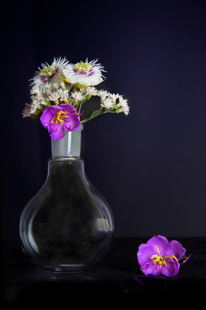 science round flask with nature bouquet of white and purple flower still life in vintage rococo black background style