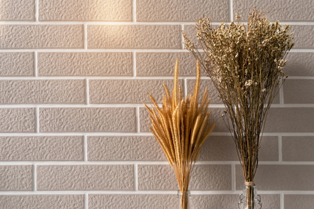 brown dry grass and small flower with soft light brick wall interior background