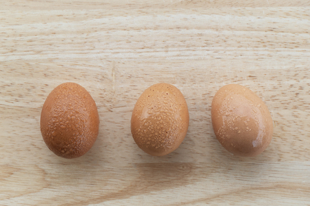 three of fresh eggs with water drop for food ingredient on brown nature wood in Easter day 版權商用圖片