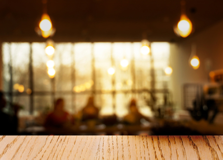 top of wood table with blur lamp and window light in the restaurant interior background