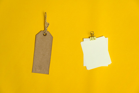 brown recycle paper tag price with paper note for business with metal clip on vibrant yellow background