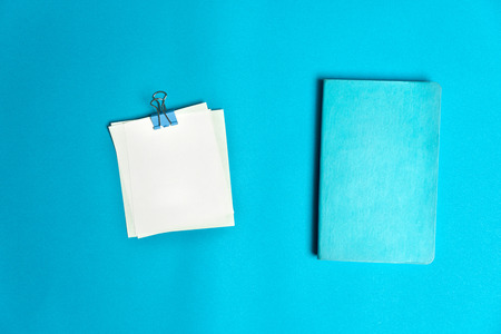 blue turquoise note book with paper pad and metal clip for colorful business or education background