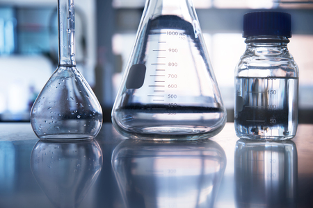 white clear flask and water in the bottle in medical science laboratory background