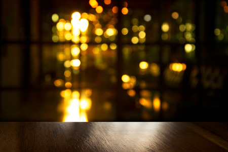 top of black wood table with blur light of party in bar or pub in the dark night background