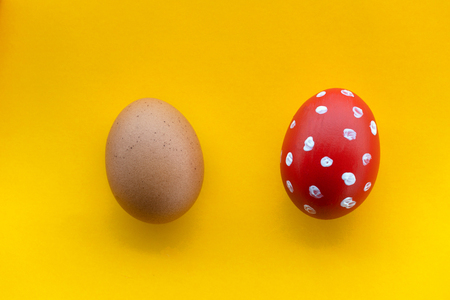two Easter holiday eggs white polka dot with red painted and raw one for decoration on colorful yellow background