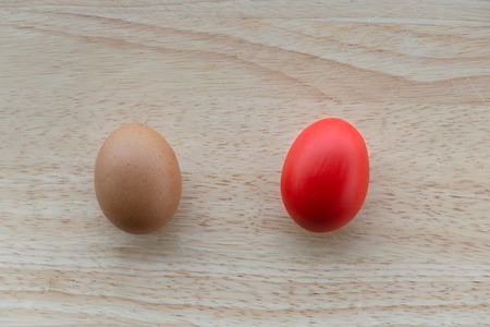 raw and red painted egg for Easter decoration or food on natural wood table background