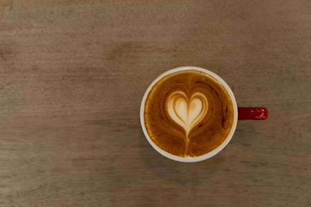 top of white heart shape of milk hot cappuccino coffee drink in red ceramic cup on wood table background Foto de archivo - 126281108