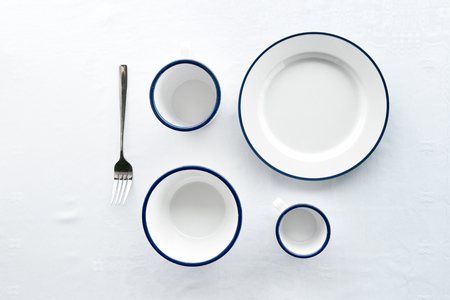 minimalism top or flat lay view of white blue set of dish mug cup fork for dinner on white tablecloth Foto de archivo - 126281116