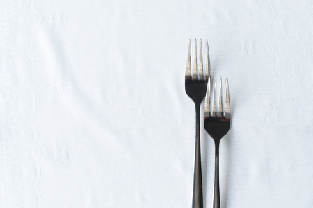 two of metal stainless steel fork on clean white tablecloth for food dinner background Foto de archivo - 126281121