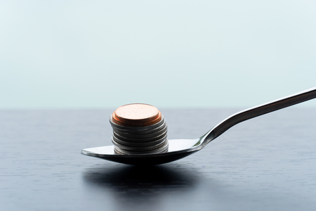 single metal teaspoon with silver and bronze coin money pile for food capitalism business concept financial background Foto de archivo - 126281158