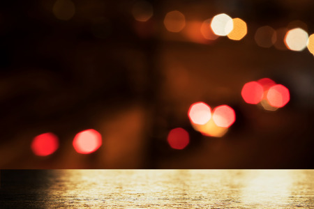 top of golden light on wood table with blur city red orange bokeh street light in the dark night background Foto de archivo - 126281177