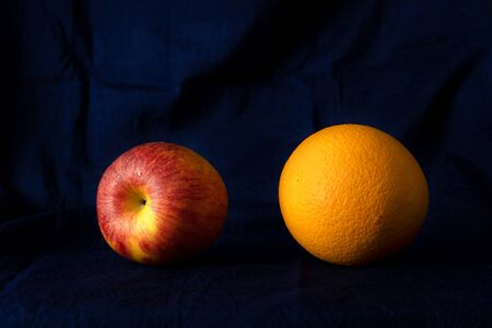 colorful red apple and orange classical still life food fruit with dark silk blue fabric background Foto de archivo - 126281246