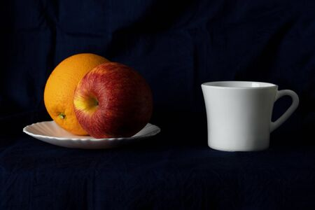 apple and orange on white ceramic vintage plate and cup of coffee or hot drink still life in classical rococo or baroque style on dark background