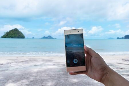 woman hand take a photo of sea water landscape by mobile phone of the summer sea beach background