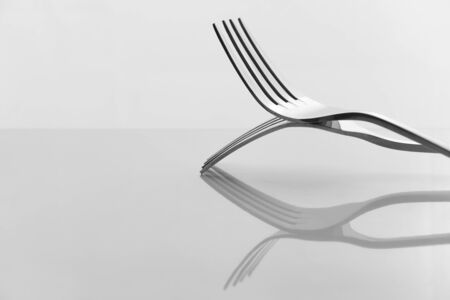 luxury two shiny silver metal fork for food dinner reflection still life on white background Imagens