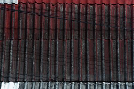 old grunge red black roof of house construction texture with electric line wire background