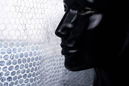 profile portrait of black woman mannequin with white burble wrap plastic fashion background