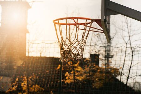 outdoor basketball hoop for team sport with orange natural light in tree autumn background