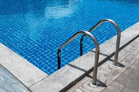 metal stainless steel ladder in summer blue swimming pool surface water for vacation travel refreshment background Imagens