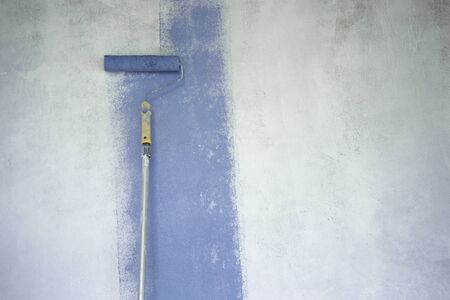 blue color stripe by long paint roller brush on white primer cement wall process of home decoration and construction background Imagens
