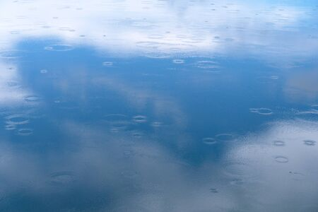 light blue reflection sky and cloud on the texture of water with ripples from raindrop nature background