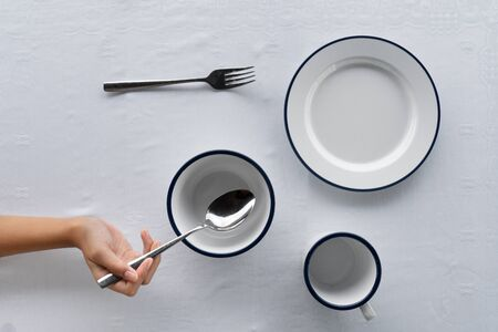 set of white dish bowl cup on food dining table with fork and woman hand holding metal spoon on tablecloth background