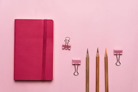 pink notebook and paper clip and wood pencil for education and business pastel background