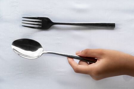 girl hand holding silver spoon and fork on luxury white tablecloth food dining background