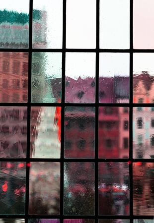 blur red pink green classic building city view from interior classic rough transparent glass window architecture background Imagens