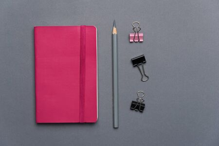 dark pink notebook with grey pencil and paper clip for business or school background