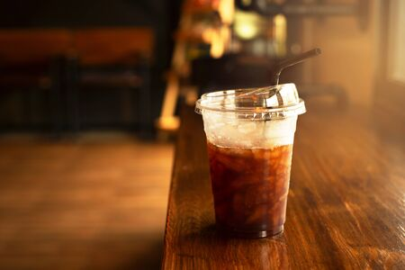 cold ice take coffee drink glass with plastic straw on wood counter table bar in cafe or restaurant with soft light background