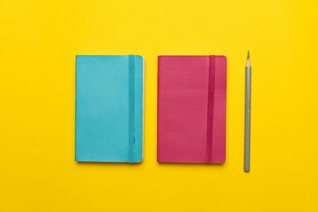 colorful blue pink notebook and grey pencil on yellow paper background for casual and creative business and education concept