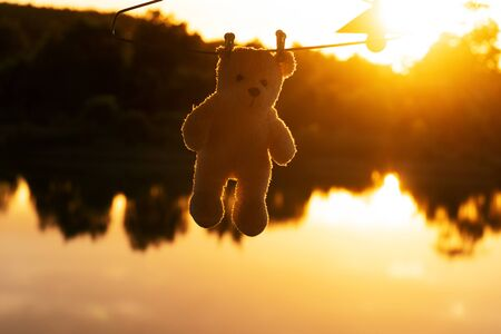 silhouette cute hanging small bear doll with orange natural summer sunset light on the lake water background