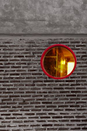round or circle red window with orange light on grey and black brick cement wall architecture detail background Imagens