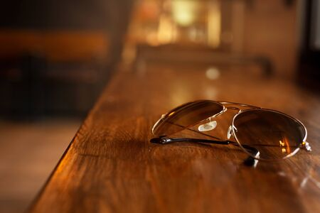 classic travel sunglasses on brown light bar wood table background