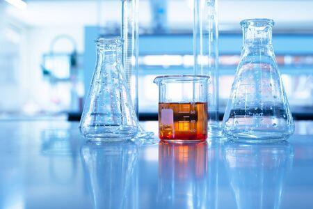 대학 교육 파란색 실험실 배경에서 화학 과학의 주황색 솔루션이 있는 유리 비커 실린더 및 플라스크