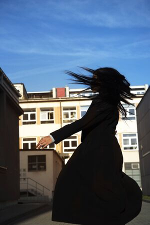 portrait of motion of turn around young African long hair woman or girl in black coat with street of city building view and blue sky