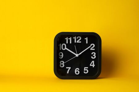 square black and white working business clock on colorful yellow background Imagens