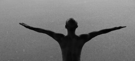 back of bald man open arm with blur raining in nature water in black and white tone for outdoor explorer concept