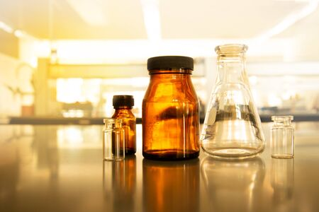 science flask and brown bottle in vintage pharmacy laboratory with soft light background