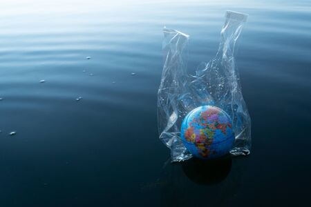 the world or earth model in a transparency plastic bag floating in dark blue marine ocean water for environmental pollution planet protection concept