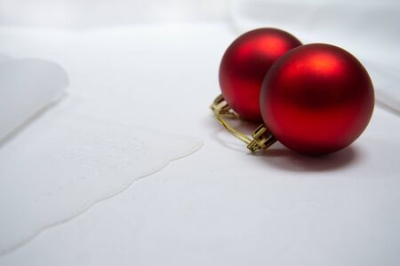 two red golden Christmas ball on white table cloth fabric background