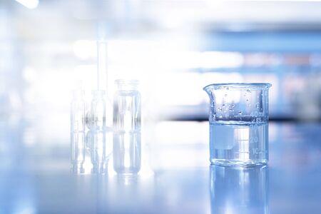 Glasbecher im weichen blauen Wissenschaftschemie-Laborhintergrund Standard-Bild