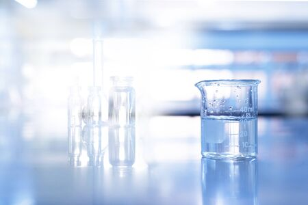 glass beaker in soft blue science chemistry laboratory background Foto de archivo